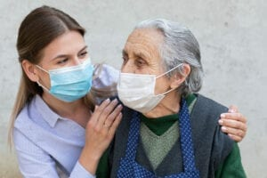 Caregiver with elderly ill woman wearing mask In-Home Caregivers